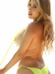 Busty babe Erika shows off her big tits in a very skimpy yellow string bikini