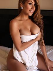 Sophia teases naked in bed with just a white sheet covering her big breasts