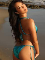 Asian babe Hoshi shows off her body at the beach in a shiny blue string bikini