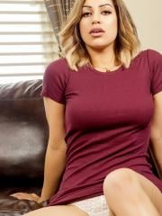 Busty babe Briana Lee strips out of her burgundy dress on the couch