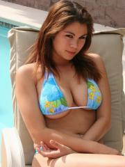Busty babe Mai Ly teases with her huge boobs in a skimpy string bikini