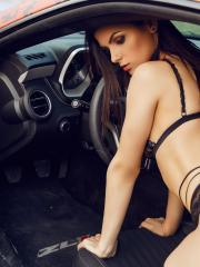 Brunette babe Eve Thompson poses with cars