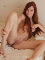 Redhead beauty Mia Sollis strips on the bed baring her pink, pussy