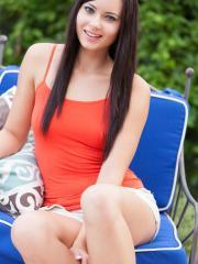 Beautiful brunette Natasha Belle slowly strips outside in her orange top