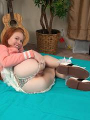 Playful redhead Dolly Little shoves a big glass dildo inside her tight pussy