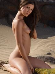 Caprice drops her yellow shawl on the sand to reveal her gorgeous nude body