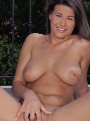 Busty brunette Chintya Doll gets naked and rubs one out outside