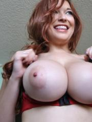 Busty redhead beauty Tessa Fowler takes a moment to expose her huge tits