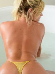Gisele gets in a hot sensual bath with her gold bikini and suction cup dildo